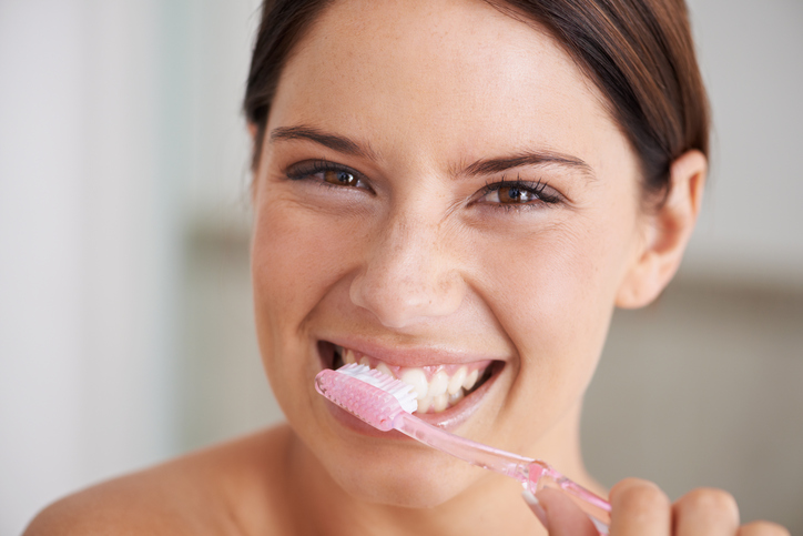 A woman smiling while brushing her teeth who has great Dental Hygiene in Surprise AZ.
